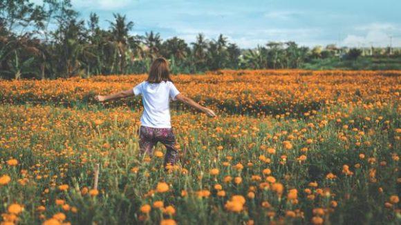 Menopausa: mulher anda com os braços abertos em campo de flores laranjas