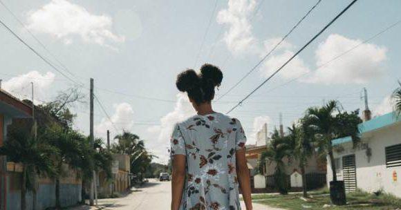 Ser menina: menina negra de costas anda por rua vazia