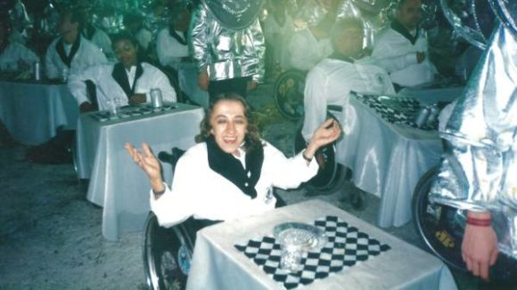 Descrição da imagem: foto colorida de Leandra em um desfile de Carnaval. Ela está sentada em sua cadeira de rodas sorrindo, com os braços abertos virados para cima. Seus cabelos e olhos são castanhos claros. Sua fantasia é uma camisa na branca com a gola na cor preta. Na frente da cadeira de rodas está uma parte da alegoria da fantasia: uma mesa de bar com uma toalha xadrez (preta e branca), um copo e um prato. Ao fundo da imagem estão várias pessoas (homens e mulheres) com deficiência que usam a mesma fantasia. E ao lado deles estão os voluntários (em pé) com outras fantasias na cor prata. Crédito da imagem: arquivo pessoal.