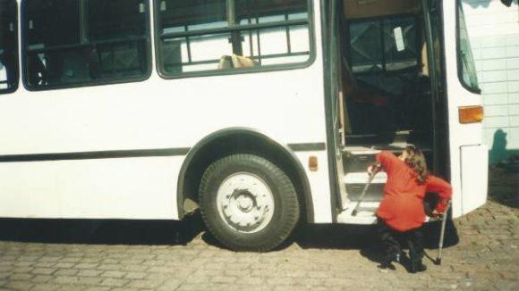 Leandra está com 22 anos trabalhando como jornalista em uma de suas primeiras reportagens em que denuncia a total falta de acessibilidade física nos meios de transportes públicos (ônibus) na cidade de SP. A foto mostra Leandra de costas tentando subir nos degraus da escada do ônibus. Ela está com uma das mãos levantadas colocando a muleta em cima de um degrau e a outra mão no chão. O ônibus na cor branca está com a porta da entrada aberta e estacionado. O tamanho do ônibus e principalmente dos degraus evidenciam a dificuldade gritante de uma pessoa com deficiência como Leandra (que tem 96 centímetros) em usar o veiculo de transporte. Leandra veste uma blusa vermelha, uma calça preta e tem a pele branca, os olhos e cabelos castanhos.